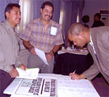 Strikers Guadeloupe Alva and Octavio Morales collect signatures on a letter/poster expressing delegates' support for their struggle